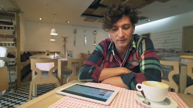 Man listening to music with headphones and digital tablet.