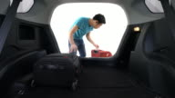 Man Loading Luggage Into Boot of Car