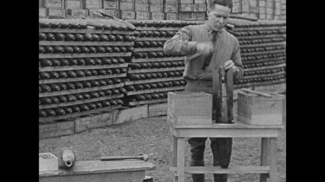 MS man loads explosive powder into bomb with funnel racks of bombs are behind him / CU stuffs caps into end of bomb / men of the United States Army...