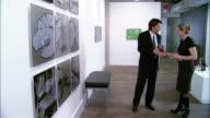 Man looking at artwork at gallery opening / woman greeting man