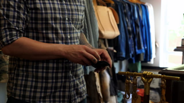 MS TD TU Man looking at leather wallet while shopping in mens boutique