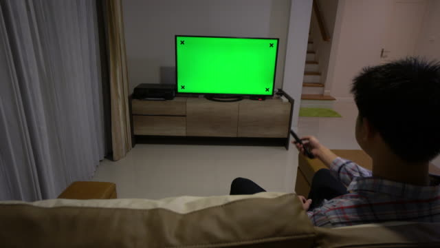Man looking at Television With Green Screen