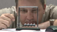 man looking bored playing with kinetic balls