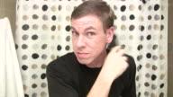 Man looking into camera brushing hair