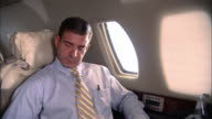 MS man looking out window on corporate jet/ air hostess talking to man