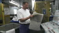 MS PAN Man looking through newspaper at printing plant, San Francisco, California, USA / AUDIO