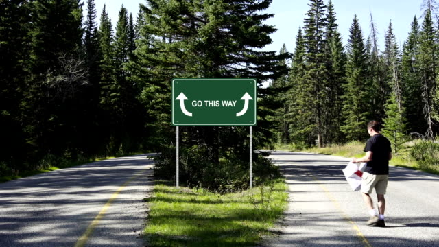 Man looks at road sign for directions
