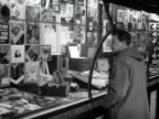 A man looks at the window displays of a record shop