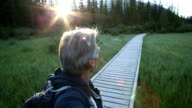 Man looks off down mountain boardwalk at sunrise