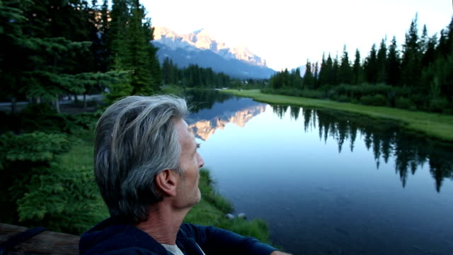 Man looks off down mountain pond at sunrise