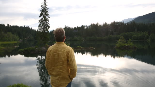 Man looks out across mountain lake, at sunrise