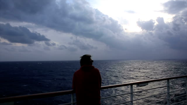 Man looks out as storm rages above Mediterranean Sea, ship view