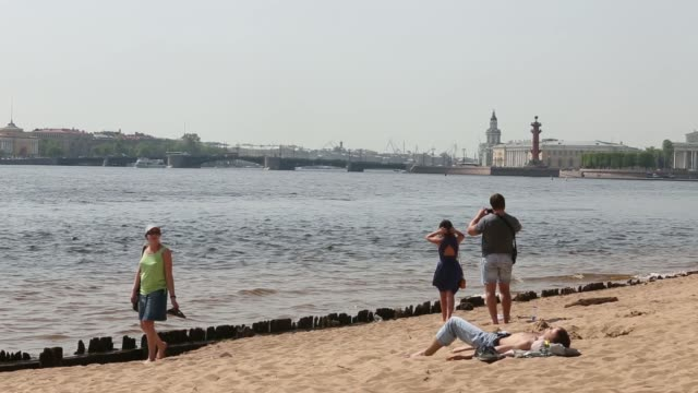 A man looks out at the River Neva in Saint Petersburg Russia on Tuesday May 20 Sunbathers relax on a sandy beach beside the River Neva A tourist boat...