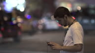 A man looks up to the oncoming traffic and walks off.  He is texting or playing with his phone