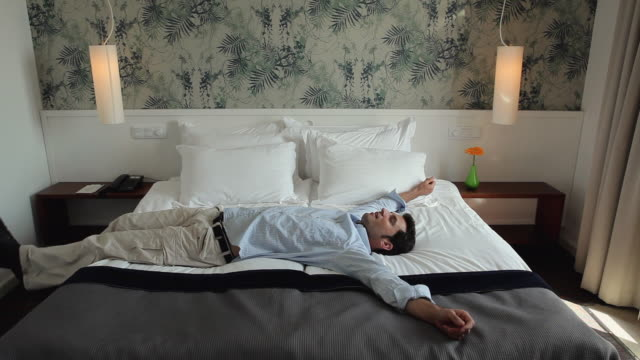 MS Man lying down on hotel bed and removing shoes / Golf De Son Termes, Bunyola, Mallorca, Baleares, Spain