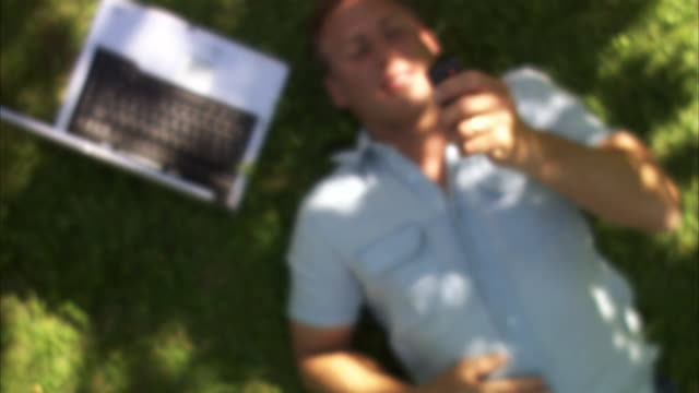 Man lying on a lawn with a laptop next to him reading an sms Sweden.