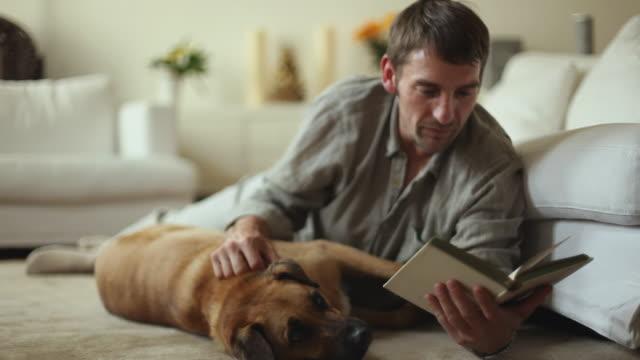 WS Man lying on floor, stroking dog and reading book / Potsdam, Brandenburg, Germany