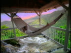 COMPOSITE man lying on hammock on porch overlooking hills with streams under hammock / Jamaica