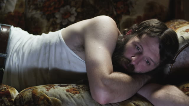 MS PAN Man lying on sofa, watching television, Orem, Utah, USA