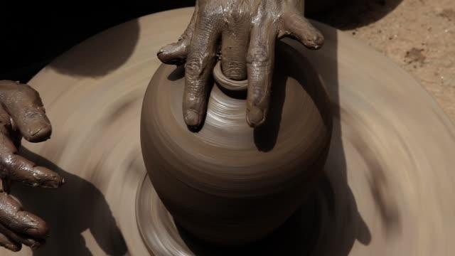 Man making a earthen pot on a pottery wheel