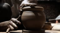 Man making a earthen pot on a pottery wheel
