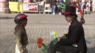 MS Man making balloon animals on street, girl standing beside and talking / Portland, Oregon, USA