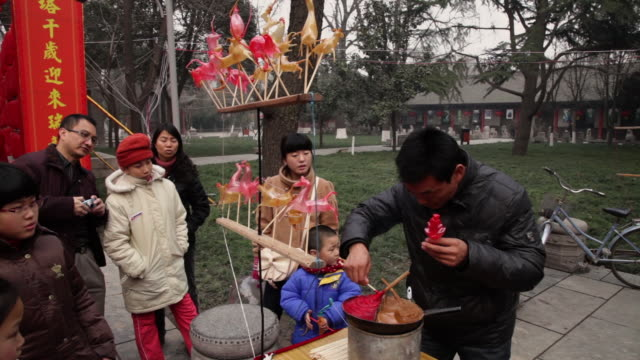 MS Man making sugar figurine for sale at temple fair to celebrate Chinese spring festival / xi'an, shaanxi, china