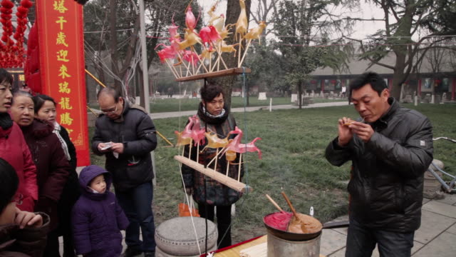 MS PAN ZI Man making sugar figurine for sale at temple fair to celebrate Chinese spring festival / xi'an, shaanxi, china