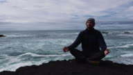 Man meditating on a rocky shore