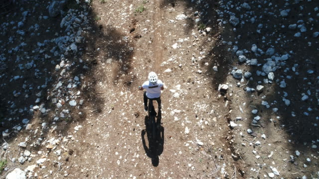 Man mountainbiker rides on a sports bicycle on a forest trail.