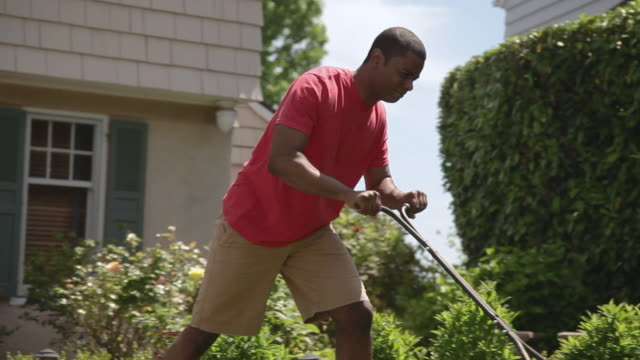 MS PAN Man mowing lawn with manual mower / Portland, Oregon, United States