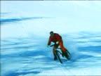 Man on bike wearing red ski suit rides down ski slope and skid spraying snow towards camera