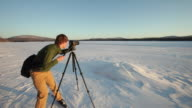 WS TU Man on cross country skis taking photos of sunset on a frozen lake / Flagstaff, Maine, USA