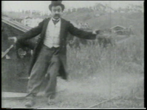 B/W 1915 man (Chester Conklin) on grass near cannon standing up + stumbling around / short