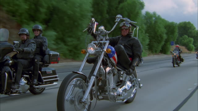 Man on Harley Davidson bike raises his thumb to camera while riding down freeway with gang of bikers, California Available in HD.