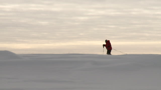 WS of man on horizon pulling pack sled across snowy landscape / South Pole, Antarctica
