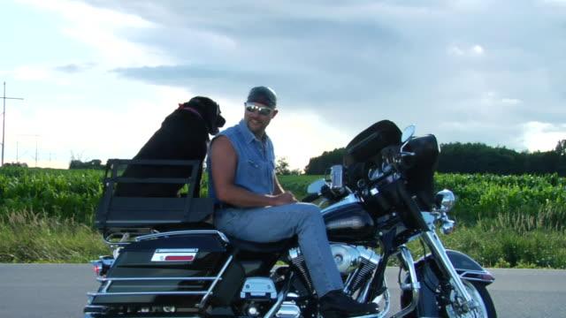 MS ZO T/L Man on motorcycle parked on roadside with dog on back/ ZI WS Man on motorcycle with dog/ Appleton, Wisconsin