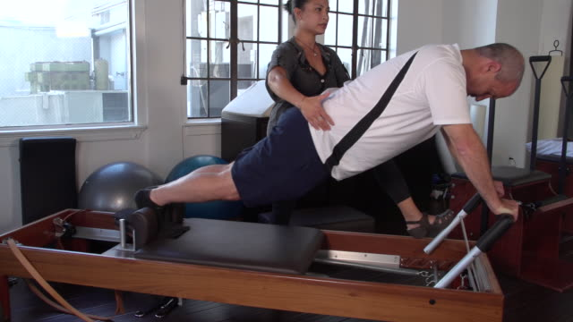 'MS Man on pilates reformer doing leg exercise with female instructor / Beverly Hills, California, United States'