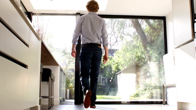 Man opening large glass door to look outside