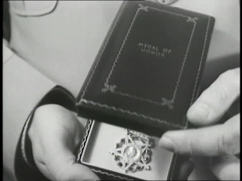 A man opens a Medal of Honor box revealing the medal inside