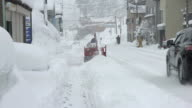 Man operates snow blower on deep snow drifts during blizzard in northern Japan