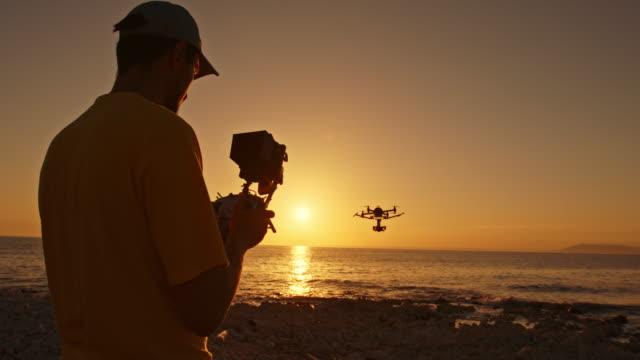 Man die een drone van het strand bij zonsondergang