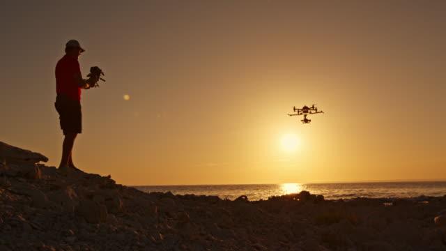 Man verkar en drönare som landar på stranden vid solnedgången