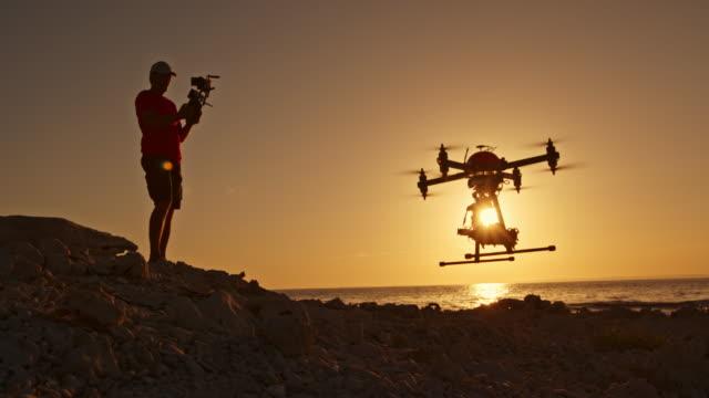 DS-Mann Betrieb eine Drohne abheben vom Strand bei Sonnenuntergang