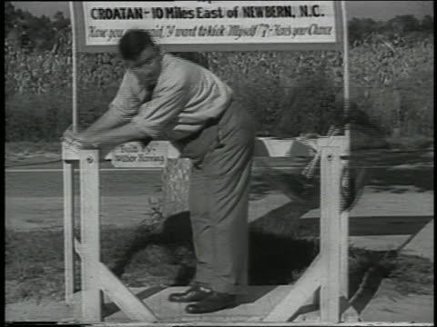 B/W 1938 man operating buttocks-kicking contraption