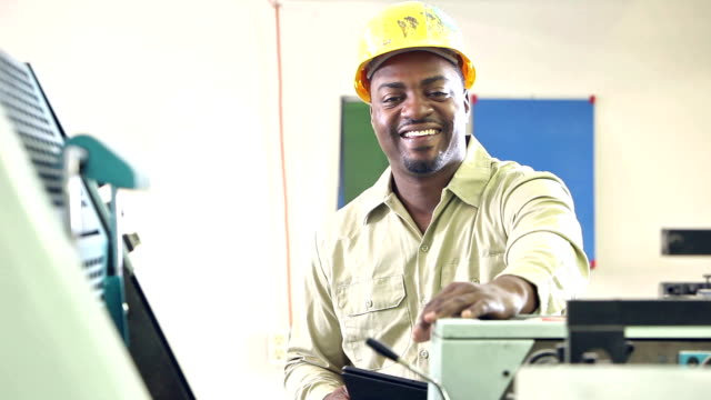Man operating printing press, setting controls