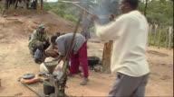 MS ZO Man operating sunflower press, people in background / Mpika, Zambia