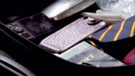 A man packs his suitcase and adds his toiletry bag.