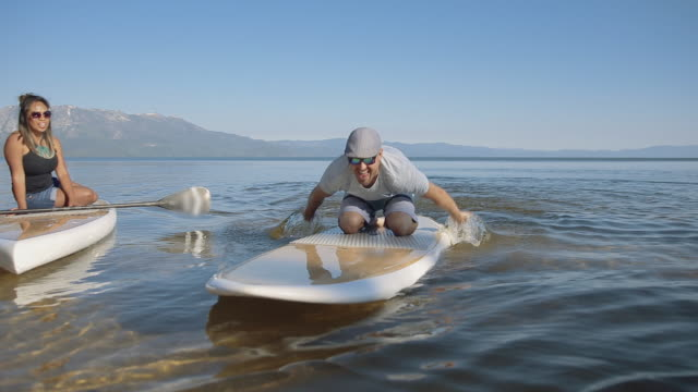 Man paddle boarding on Lake Tahoe with his wife