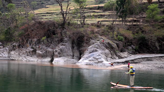 MS Man paddleboarding on calm river in front of terraced fields with native people on shore / Ramnagar, India